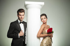 Pares elegantes que levantam perto da coluna imagens de stock royalty free