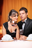 Pares elegantes que sentam-se em uma tabela em um restaurante Imagens de Stock Royalty Free