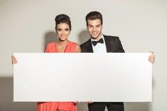 Pares elegantes que sorriem ao guardar uma placa branca Fotografia de Stock Royalty Free