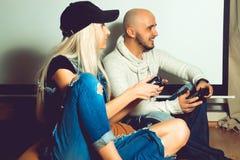 Pares elegantes que têm o divertimento e que jogam jogos de computador Foto de Stock
