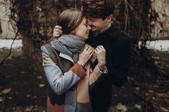 Pares elegantes románticos que abrazan suavemente en parque del otoño hombre y w Imagen de archivo libre de regalías