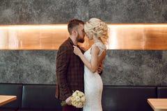 Pares em abraços e em beijos do amor em seu dia do casamento Noivo do moderno e a noiva, o amor e a lealdade O par ideal está pre fotografia de stock