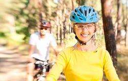 Pares em bicicletas na floresta ensolarada imagem de stock