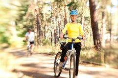 Pares em bicicletas na floresta ensolarada foto de stock royalty free