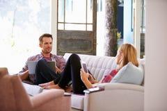 Pares em casa em dispositivos de Sofa In Lounge Using Digital imagens de stock