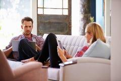 Pares em casa em dispositivos de Sofa In Lounge Using Digital fotografia de stock