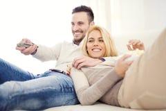 Pares em casa que prestam atenção à tevê Fotos de Stock Royalty Free