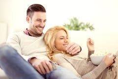 Pares em casa que prestam atenção à tevê Foto de Stock Royalty Free