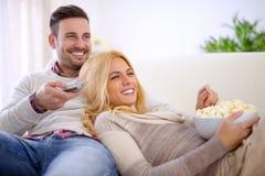 Pares em casa que prestam atenção à tevê Imagens de Stock Royalty Free