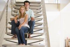 Pares em casa que sentam-se em escadas Foto de Stock