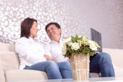 Pares em casa que sentam-se no sofá imagens de stock