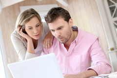 Pares em casa que usam o portátil foto de stock royalty free