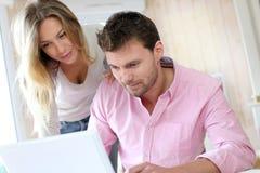 Pares em casa que usam o portátil fotos de stock royalty free