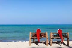 Pares em chapéus de Santa na praia tropical Fotos de Stock Royalty Free