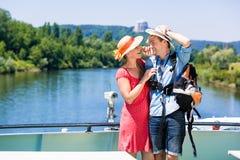 Pares em chapéus vestindo do sol do cruzeiro do rio no verão foto de stock royalty free