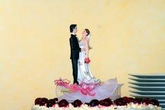Pares em um bolo de casamento Imagem de Stock Royalty Free