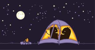 Pares em uma barraca de acampamento em a noite Fotos de Stock Royalty Free