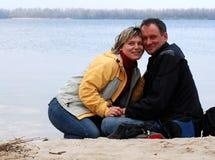 Pares em uma costa do rio Fotografia de Stock Royalty Free