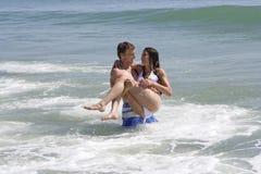 Pares em uma praia Imagem de Stock
