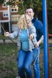 Pares embarazadas de los jóvenes en la primavera Fotos de archivo libres de regalías