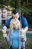 Pares embarazadas de los jóvenes en la primavera Foto de archivo libre de regalías