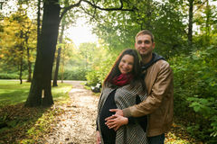 Pares embarazadas de los jóvenes en otoño afuera Fotografía de archivo libre de regalías