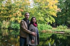 Pares embarazadas de los jóvenes en un parque de la caída Foto de archivo