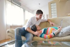 Pares embarazadas en casa usando la tableta Foto de archivo libre de regalías