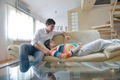 Pares embarazadas en casa usando la tableta Fotos de archivo