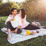 Pares embarazadas en comida campestre Foto de archivo