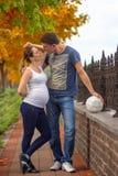 Pares embarazadas - en el parque del otoño con la bola del fútbol Fotos de archivo libres de regalías