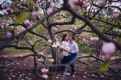 Pares embarazadas en jardín de la magnolia fotos de archivo libres de regalías