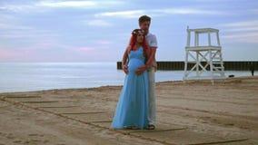 Pares embarazadas en la playa del mar en la salida del sol Pares del amor que abrazan en el mar de la playa almacen de video