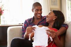Pares embarazadas en la ropa del bebé de Sofa At Home Looking At Foto de archivo libre de regalías