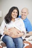 Pares embarazadas felices en casa Imagen de archivo
