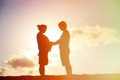 Pares embarazadas felices en la playa de la puesta del sol Imagen de archivo