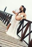 Pares embarazadas felices en la ropa blanca en la costa de mar en el puente de madera Fotos de archivo libres de regalías