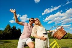 Pares embarazadas felices en vidrios coloreados brillantes en una bicicleta adentro Fotos de archivo libres de regalías