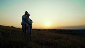 Pares embarazadas felices jovenes románticos que abrazan en naturaleza en la puesta del sol metrajes