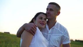 Pares embarazadas felices jovenes románticos que abrazan en naturaleza en la puesta del sol almacen de video