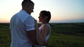 Pares embarazadas felices jovenes románticos que abrazan en naturaleza en la puesta del sol almacen de metraje de vídeo