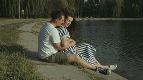 Pares embarazadas felices que se relajan por el lago en parque almacen de video