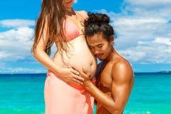 Pares embarazadas felices y de los jóvenes que se divierten en una playa tropical Foto de archivo libre de regalías
