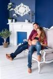 Pares embarazadas hermosos que se relajan en el sofá en casa junto Familia, hombre feliz y mujer contando con a un niño Fotografía de archivo