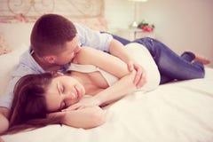 Pares embarazadas jovenes felices en dormitorio Fotografía de archivo
