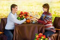 Pares embarazadas jovenes hermosos que tienen comida campestre en parque del otoño Ha Imagenes de archivo