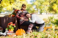 Pares embarazadas jovenes hermosos que tienen comida campestre en parque del otoño Ha Fotos de archivo
