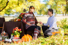 Pares embarazadas jovenes hermosos que tienen comida campestre en parque del otoño Ha Foto de archivo libre de regalías