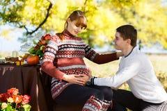 Pares embarazadas jovenes hermosos que tienen comida campestre en parque del otoño Ha Fotografía de archivo libre de regalías