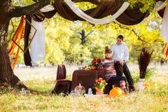 Pares embarazadas jovenes hermosos que tienen comida campestre en parque del otoño Ha Imagen de archivo libre de regalías